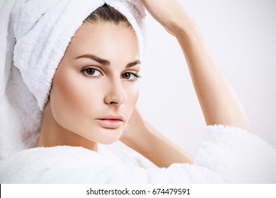 Young woman face with perfect skin and bath towel on head. Close-up.