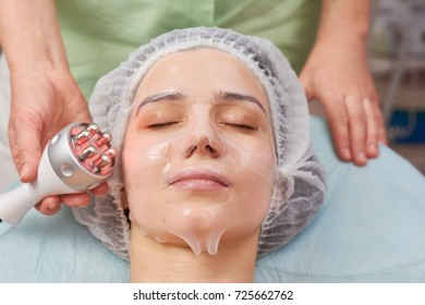 Young woman, facial collagen mask. Rf skin tightening device, hand.