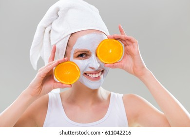 Young woman with facial mask holding slices of orange on gray background.Woman skin care