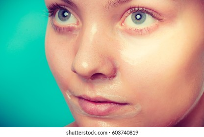 Young woman in facial peel off mask. Peeling. Beauty and skin care. Studio shot on green
