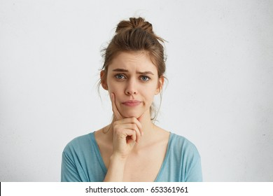 Young woman with fair hair and blue eyes frowning her eyebrows holding index finger on chin having doubt and suspicion feeling sceptical about something. Human emotions and expressions concept