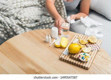 Young woman fall ill cold and flu was treated at home on the couch. Takes medication and drinks with a glass of water.