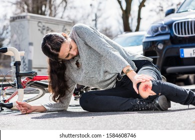 Young woman fallen down on the ground with a bleeding scrape on the knee after severe injury in bicycle accident on the street