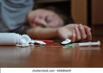 Young woman fallen on the floor with drug essentials next to her