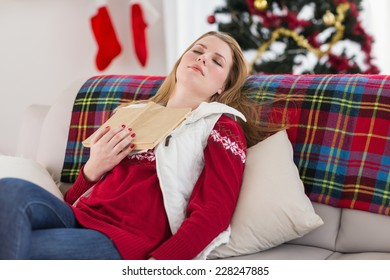 Young woman falling asleep while reading at home in the living room