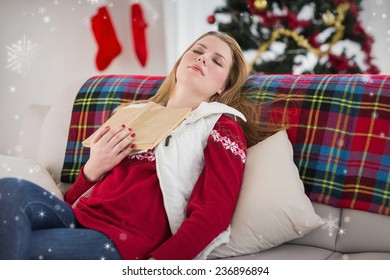 Young woman falling asleep while reading against snow falling