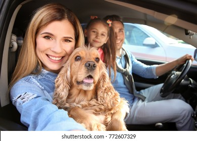 Young woman with family and dog taking selfie in car