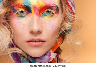 Young woman with fantasy bright make up. Unusual face art studio shot.