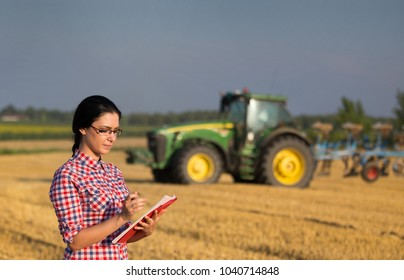 Young woman farmer standing on wheat field during harvest. Tractor in background
