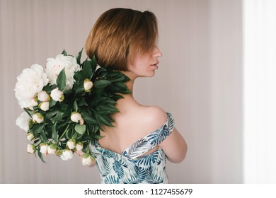 Young woman in fashon dress holding bouquet of beautiful white peonies flowers behind her back St. Valentine's Day, International Women's Day concept.