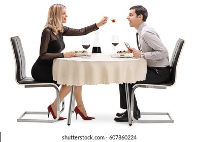 Young woman feeding her boyfriend salad at a restaurant table isolated on white background