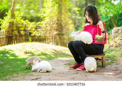 Young woman feeding her rabbit.