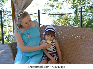 The young woman feeds the three-year-old daughter with apple in the open air