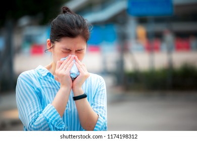 Young woman feel allergy and wiping nose on street