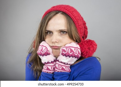 Young woman feeling cold trying to keep warm, shaking and shivering, wearing knitted gloves and hat over gray background