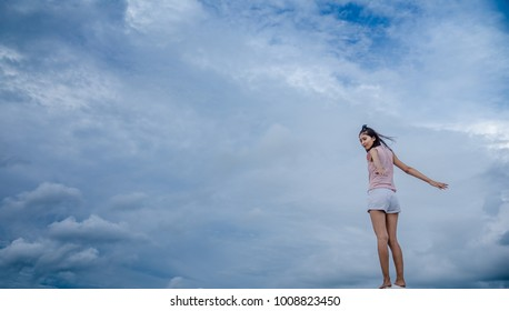 Young woman feeling free in blue sky background