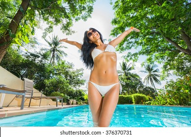 Young woman feeling happy and fun relaxing in swimming pool. Tropical vacation.