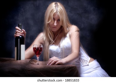 young woman feeling lonely with bottle of wine and glass
