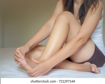 Young woman feeling pain in her foot at home. Healthcare and medical concept.