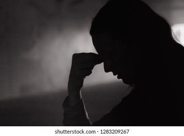 Young woman feeling sad in a dark setting.