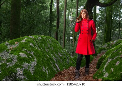 Young woman feeling sad walking alone on forest path wearing red long coat or overcoat. Girl passes track on walk in woods of nature park during fall, autumn or winter