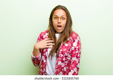 young woman feeling shocked, astonished and surprised, with hand on chest and open mouth, saying who, me? against green background