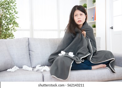 young woman feeling sick or sad wrapped in blanket and sitting on sofa at home, staring blankly ahead. medical and health concept. mixed race asian chinese model.