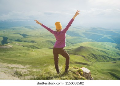 Young woman feeling strong and confident on the outdoor against green valley