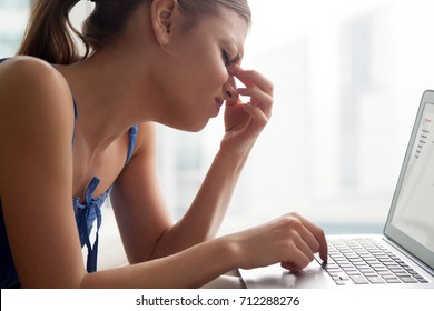Young woman feeling tired, massaging nose bridge, suffering from migraine or eye strain, exhausted lady having sudden headache, eyesight problem after long work study on computer, head shot side view