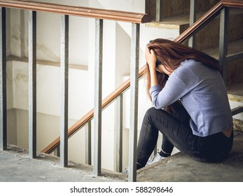 Young woman feeling upset, disappointed, bad, broken heart, stressed sitting alone on stair crying