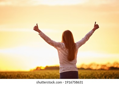 Young woman feeling victorious facing the beautiful sunset.