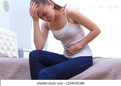 Young woman feels bad and experiences abdominal pain during the period of PMS and menstruation. Painful menstruation. Inflammation and Bladder Infection