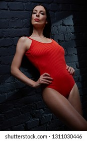 Young woman - female dancer in red with dramatic expression against black wall, portrait.