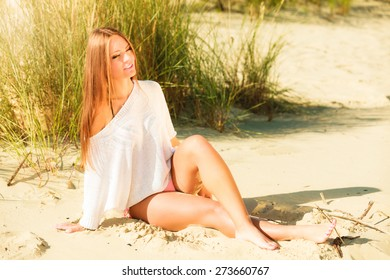Young woman female model in full length posing outdoor on background of grassy dunes
