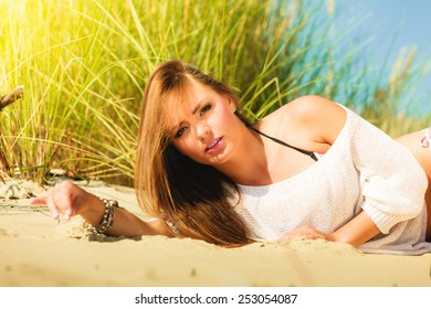 Young woman female model posing outdoor on background of dunes sky and grass
