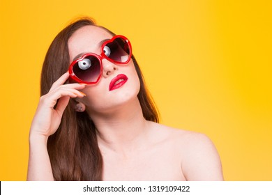 4e7b60ac2c Young woman female model wearing red heart shaped sun glasses on yellow  background. summer happy