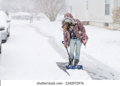 Young woman, female in winter coat cleaning, shoveling driveway, street from snow in heavy snowing snowstorm with shovel, residential houses, cars parked on road