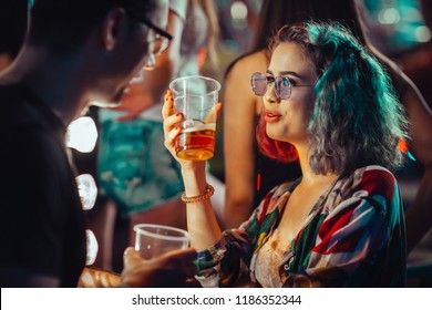 Young woman at the festival drinking beer with boyfriend