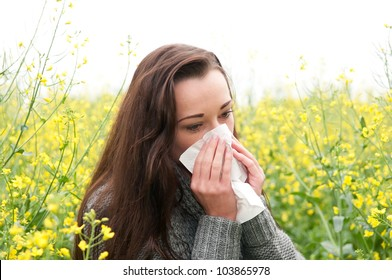 young woman in field  has hay fever