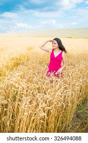 young woman in the field, looking into the distanc