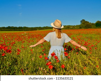 Young woman in field of red flowers wearing a sunhat. Dalkeith, Scotland UK. July 2018