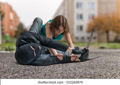 Young woman is fighting with armed thief with knife. Self defense concept.