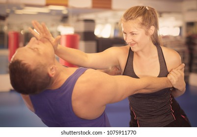 Young woman is fighting with trainer on the self-defense course for woman in sport club
