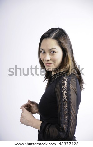 Young woman of filipino ethnicity is standing sideways and looking at camera.