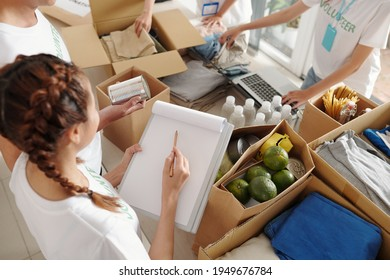 Young woman filling document when team of volunteers packing clothes, food and waterr in big cardboard boxed for people who lost their job due to coronavirus pandemic