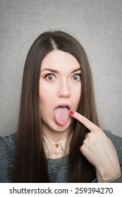 young woman with finger on tongue