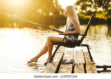 Young woman fishing at the lake. Hobby quality time