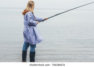 young woman fishing on cloudy autumn day
