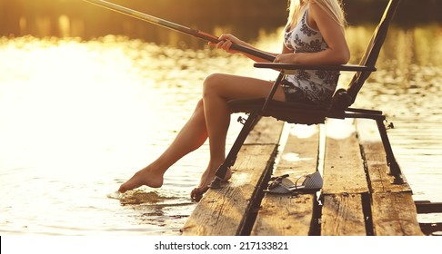 Young woman fishing on a summer sunny evening.