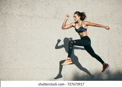 Photo of Young woman with fit body jumping and running against grey background. Female model in sportswear exercising outdoors.